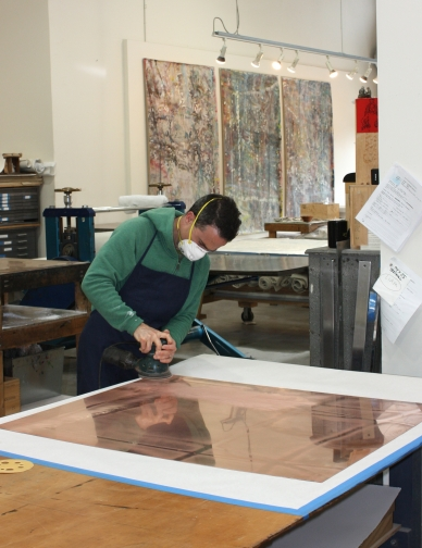 Liam in the studio sanding a copper plate